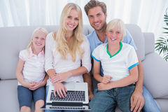 Cheerful family using laptop in the living room Stock Photos