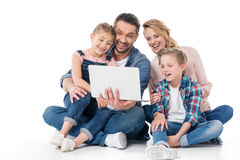 Cheerful family using laptop while sitting on floor. Isolated on white stock images