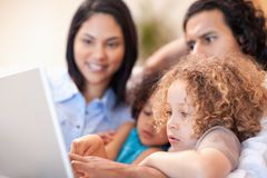 Cheerful family using laptop together Stock Photo
