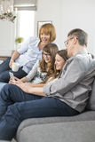 Cheerful family using tablet PC on sofa at home Royalty Free Stock Image