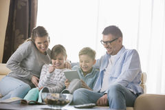 Cheerful family using tablet PC together in living room Royalty Free Stock Images