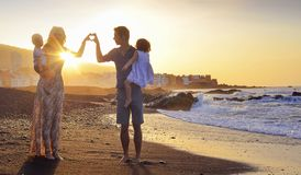 Cheerful family walking on the tropical beach stock images