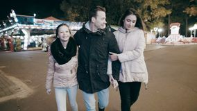 A cheerful family walks the night city. Parents connected the daughter to the amusement park on the merry-go-round. The young family came to the amusement park stock video footage