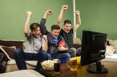 Cheerful family watching Superbowl, fist in air. Cheerful family watching Superbowl with hands in the air / touchdown royalty free stock image