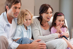 Cheerful family watching television together Stock Images