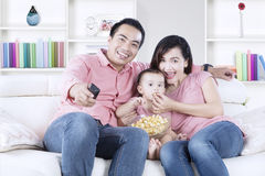 Cheerful family watching TV at home Stock Image