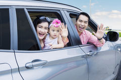 Cheerful family waving hands in the car Royalty Free Stock Images