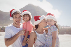 Cheerful family wearing Santa hat at beach. Cheerful family wearing Santa hat during sunny day at beach Stock Photography