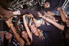 Cheerful fans lifting performer at nightclub. During music concert Stock Image