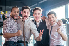 Cheerful fans watching TV and delight football. Four successful Stock Images