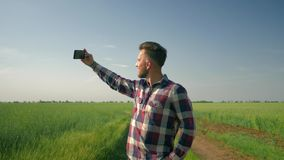 Cheerful farmer in checkered shirt hold cell phone and takes selfie photo on background of green field and blue sky. Cheerful farmer in checkered shirt hold cell stock footage