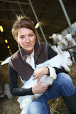 Cheerful farmer holding a baby goat Royalty Free Stock Photos