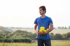 Cheerful farmer holding fresh melon crop on the field at organic eco farm. Cheerful proud farmer holding in hands fresh yellow melon crop on the field at Stock Photo