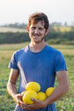 Cheerful farmer holding fresh melon crop on the field at organic eco farm. Cheerful proud smiling farmer holding in hands fresh yellow melon crop on the field Stock Photo