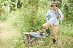 Cheerful farmer. Smiling farmer with garden tools, wheelbarrow and rope standing in his garden Royalty Free Stock Images