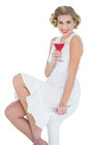 Cheerful fashion blonde model enjoying a cocktail Stock Photos