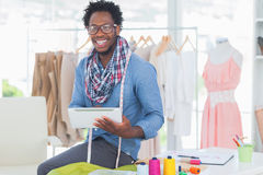 Cheerful fashion designer holding digital tablet Royalty Free Stock Photography