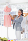 Cheerful fashion designer measuring dress on a mannequin Stock Photography