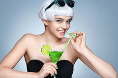 Cheerful fashion girl with glass of cocktail on blue background Royalty Free Stock Photography