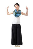 Cheerful fashion model in wide-leg pants and colorful scarf with thumbs up Royalty Free Stock Photography