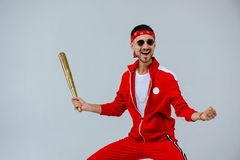 Cheerful fashionable man wearing a red sports suit in his hand a gold baseball bat is more than a little surprised. proud and succ royalty free stock photography