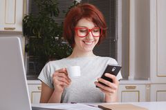 Cheerful fashionable woman with red hair, glad to view photos on social websites, has coffee break after working at laptop compute stock photos