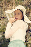 Cheerful fashionable woman in stylish hat and frock posing Stock Image