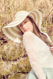 Cheerful fashionable woman in stylish hat and frock posing Stock Photos
