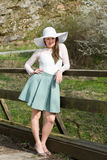 Cheerful fashionable woman in stylish hat and frock posing Stock Photo