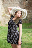 Cheerful fashionable woman in stylish hat and frock posing Royalty Free Stock Photo