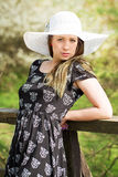 Cheerful fashionable woman in stylish hat and frock posing Stock Photography