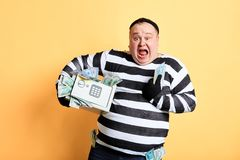 Cheerful fat criminal holding a safe full of money. robbery concept. Yellow background. happiness stock photo