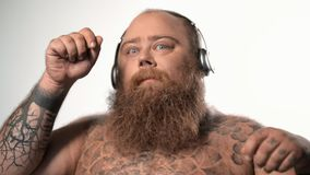 Cheerful fat hipster enjoying melody from earphones stock video