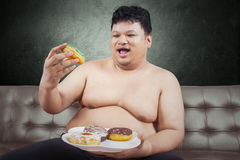 Cheerful fat man eating donuts. Cheerful fat man looking at donuts while sitting on the sofa at home Royalty Free Stock Images