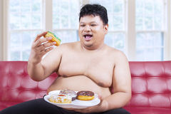 Cheerful fat man eating donuts 2. Cheerful fat man looking at donuts while sitting on the sofa at home Stock Image