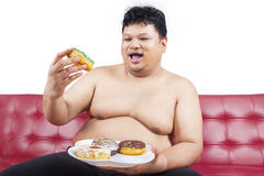 Cheerful fat man eating donuts 1. Cheerful fat man looking at donuts while sitting on the sofa at home Stock Photos