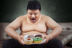 Cheerful fat man looking at donuts. While sitting on the sofa at home Stock Photography