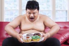 Cheerful fat man looking at donuts 2. Cheerful fat man looking at donuts while sitting on the sofa at home Stock Image