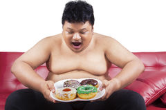 Cheerful fat man looking at donuts 1. Cheerful fat man looking at donuts while sitting on the sofa at home Stock Photography