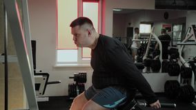 Cheerful fat man performs a wrong exercise in the gym. For the first time in a fitness club. Cheerful fat man performs a wrong exercise in the gym. For the stock video footage