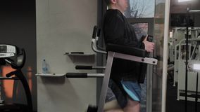 Cheerful fat man performs a wrong exercise in the gym. For the first time in a fitness club. Cheerful fat man performs a wrong exercise in the gym. For the stock video