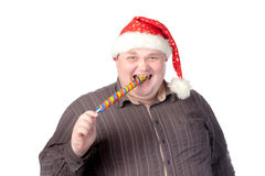 Cheerful fat man in Santa hat. Cheerful obese man in a red Santa hat chewing on a long colourful spiral lollipop with a grin on his face isolated on white Stock Image