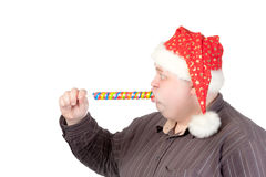 Cheerful fat man in Santa hat. Cheerful obese man in a red Santa hat chewing on a long colourful spiral lollipop with a grin on his face isolated on white Stock Photography