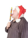 Cheerful fat man in Santa hat. Cheerful obese man in a red Santa hat chewing on a long colourful spiral lollipop with a grin on his face isolated on white Stock Photos