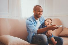 Cheerful father babysitting his child. Our weekend. Exuberant loving daddy holding a remote control and babysitting his son stock photography