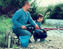 Cheerful father and boy fishing with rods Royalty Free Stock Images