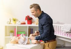 Father changing baby girl diapers. Cheerful father changing baby girl diapers royalty free stock images