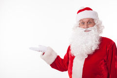 Cheerful Father Christmas is advertising something. Friendly Santa Claus is raising his hand sideways and presenting something. He is looking forward and smiling Stock Images