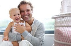 Cheerful father with cute baby laughing together Stock Image