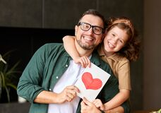 Cheerful father and daughter celebrating Fathers Day together at home